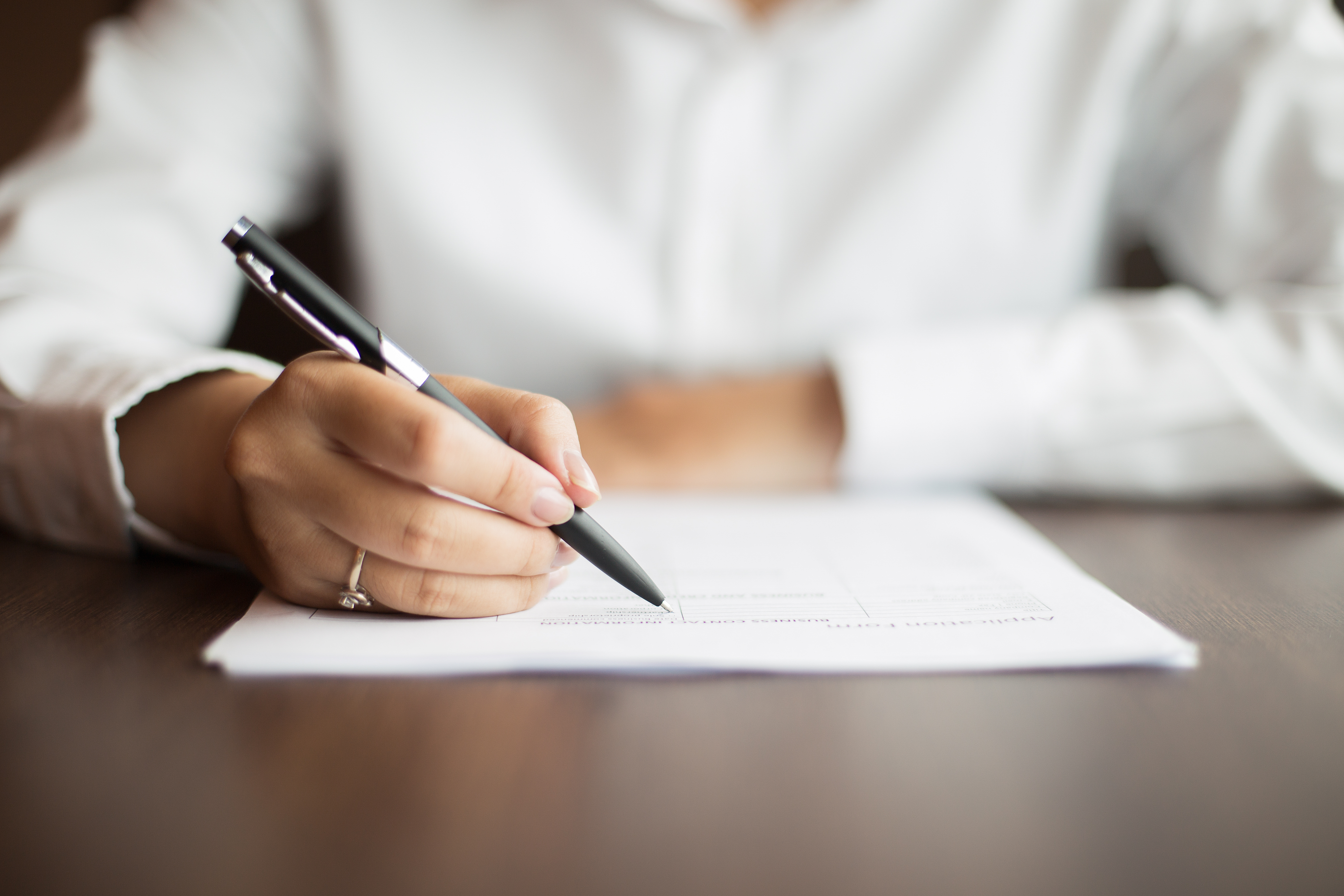 Hand of young businesswoman wearing ring and sitting at table writing on document with pen in office